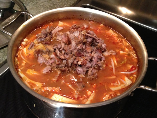 Adding the shredded pork meat to soup