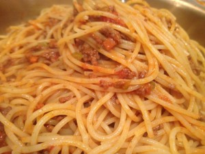 Tossing spaghetti with meat sauce